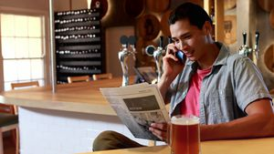 Man talking on mobile phone while reading newspaper in a restaurant 4k