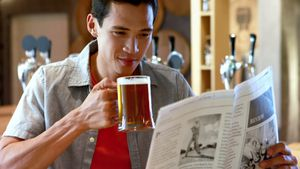 Man having beer while reading newspaper in a restaurant 4k