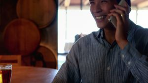 Man having beer while talking on mobile phone in a restaurant 4k