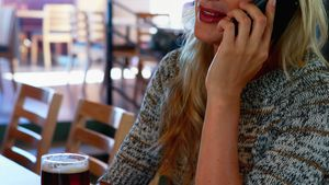 Woman talking on mobile phone while having beer at bar 4k