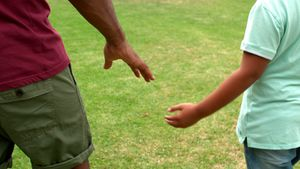 Father and son holding hands in garden