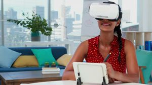 Female graphic designer in virtual reality headset using digital tablet at desk 4k