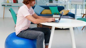 Male executive using laptop while sitting on exercise ball at desk 4k