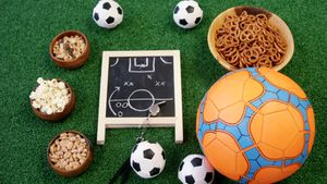 Bowl of snacks, football and slate on artificial grass 4k