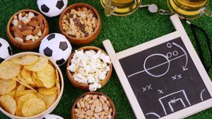 Bowl of snacks, football, beer, whistle and slate on artificial grass 4k