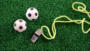 Footballs and referee whistle on artificial grass 4k