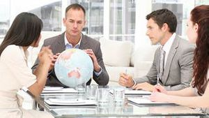 Manager holding a terrestrial globe in a meeting