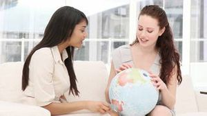 Concentrated businesswomen looking at a terrestrial globe