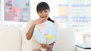 Young businesswoman looking at a terrestrial globe