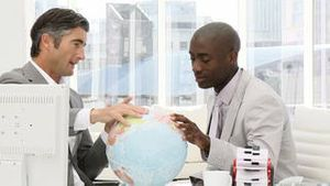 Serious businessmen looking at a terrestrial globe