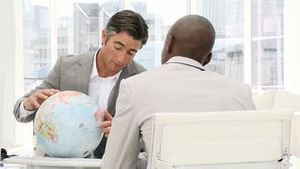 Confident businessmen looking at a terrestrial globe
