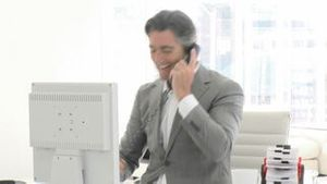 Positive business man working at a computer