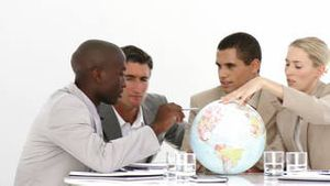 Multiethnic business people looking at a terrestrial globe