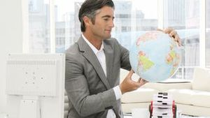 Confident businessman looking at a terrestrial globe