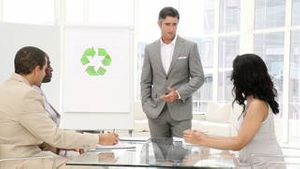 Confident businessman presenting recycling sign