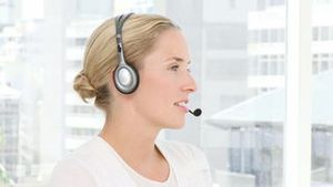 Blond business woman holding headset