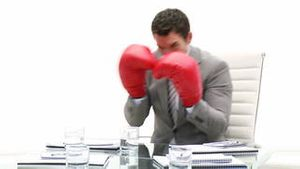 Competitive business man holding boxing gloves