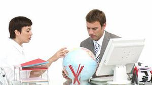 Business partners looking at a terrestrial globe