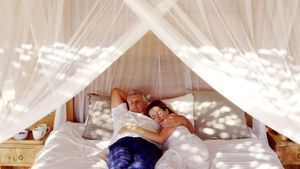 Senior couple sleeping on canopy bed 4k