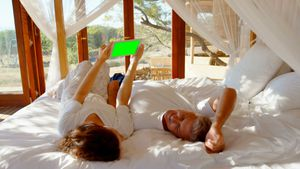 Happy couple using digital tablet on bed 4k