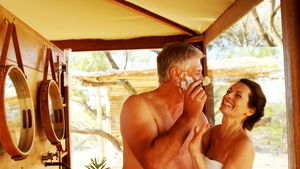Smiling couple having fun while shaving in cottage 4k