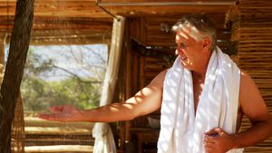 Man washing hands from shower in cottage during safari vacation 4k