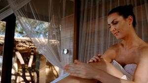 Woman applying lotion while sitting on canopy bed 4k