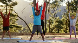 Trainer and kids performing yoga 4k