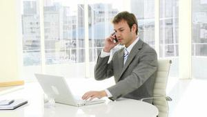 Charming businessman on phone working at a laptop