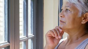 Thoughtful senior woman looking through window in bed room 4k
