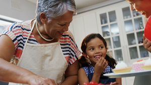Girl eating a cherry while making cupcakes with mother and granny 4k