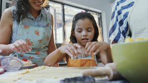 Girl learning to cut cookies with her mother and granny 4K 4k