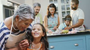 Girl interacting with granny while family preparing cookies 4k