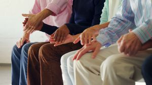 Group of senior people sitting together with holding hands 4k