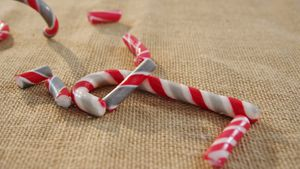 Candy cane falling on textile 4k