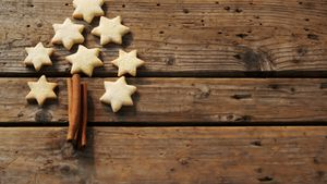 Christmas cookies and cinnamon sticks on wooden table 4k