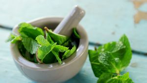 Mint leaves with mortar and pestle on wooden table 4k