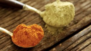 Red chili powder and coriander powder on a wooden table 4k