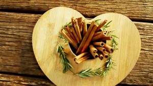 Cinnamon sticks and rosemary arranged on wooden board 4k