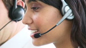 Smiling ethnic businesswoman with headset on