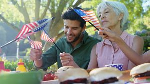 Family holding american flags during meal in the park 4k