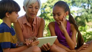 Grandmother and grand kids using digital tablet in the park 4k