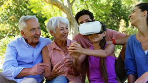 Girl using vr headset while sitting with her family 4k