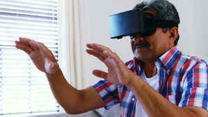 Senior man using virtual reality headset in living room 4k