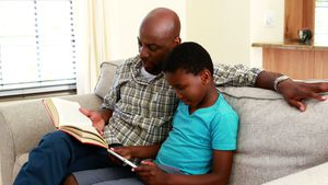 Father reading book and son using digital tablet in living room 4k