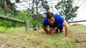 Fit man crawling under the net during obstacle course 4k