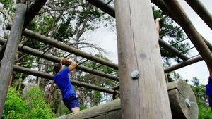 Female trainer clapping hands while fit people climbing monkey bars 4k