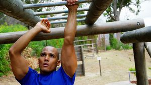 Female trainer clapping hands while fit man climbing monkey bars 4k