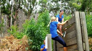 Female trainer assisting fit woman to climb over wooden wall during obstacle course 4k