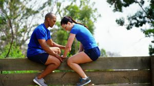 Male trainer assisting fit woman to climb over wooden wall during obstacle course 4k